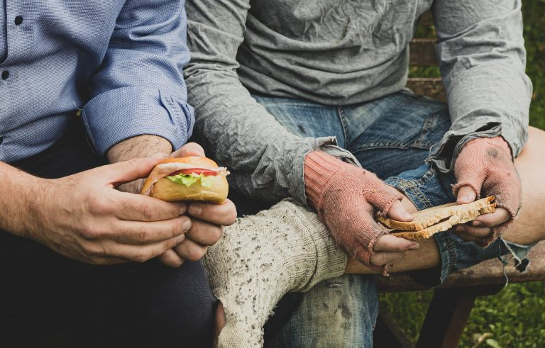 photo of homeless man eating with a person supporting them